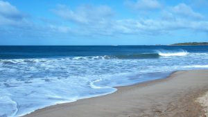 A bit of sand showing with the blue ocean and sea foam